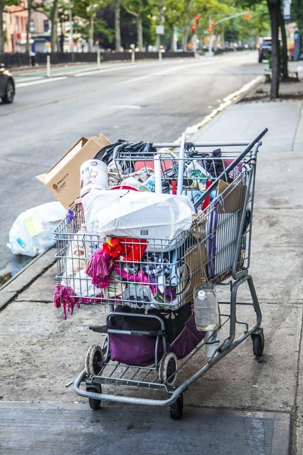 Hemlös mans shoppa vagn mycket av tillhörigheter royaltyfri bild