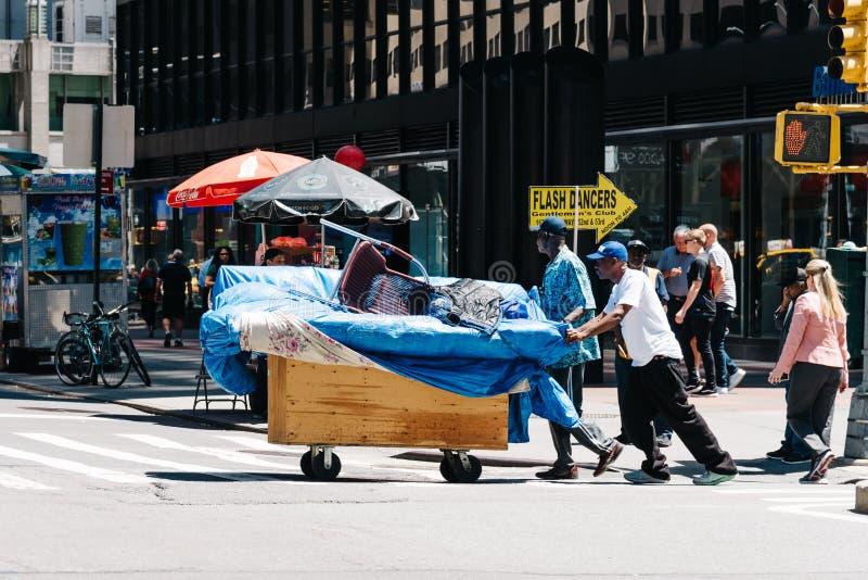 Hemlös skjutande vagnskorsning gata i Manhattan arkivbilder