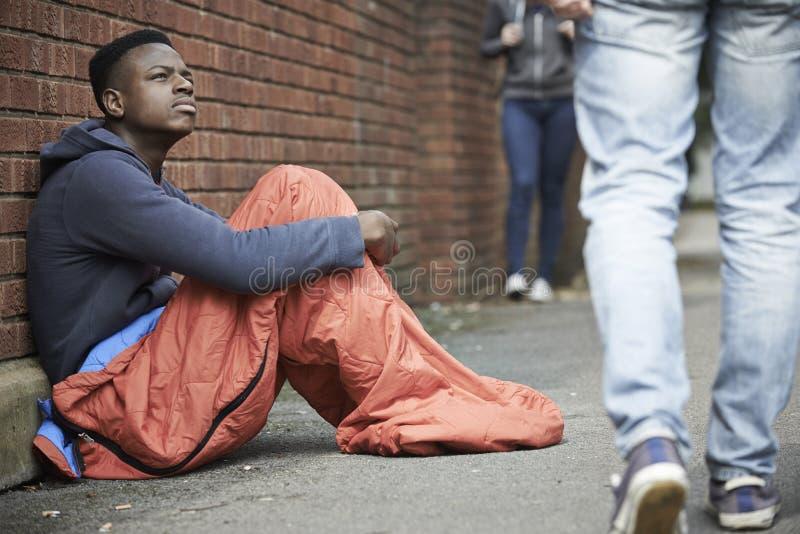 Hemlös sovsäck för tonårs- pojke på gatan arkivfoton