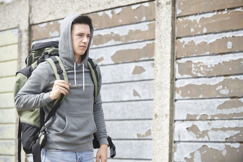 Hemlös tonårs- pojke på gatan med ryggsäcken royaltyfria bilder