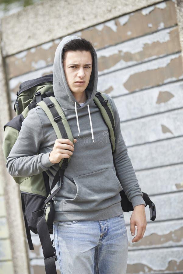 Hemlös tonårs- pojke på gatan med ryggsäcken royaltyfria foton