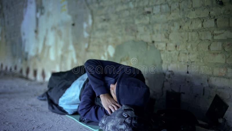 Hemlös ung man som sover på gatan, likgiltigt egoistiskt samhälle, armod royaltyfri bild