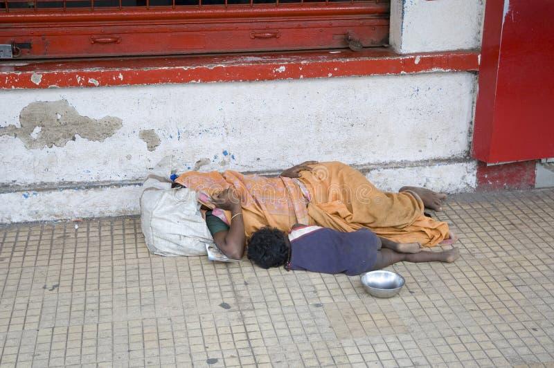 Hemlösa tiggare moder och barn som sover på vägen arkivfoto