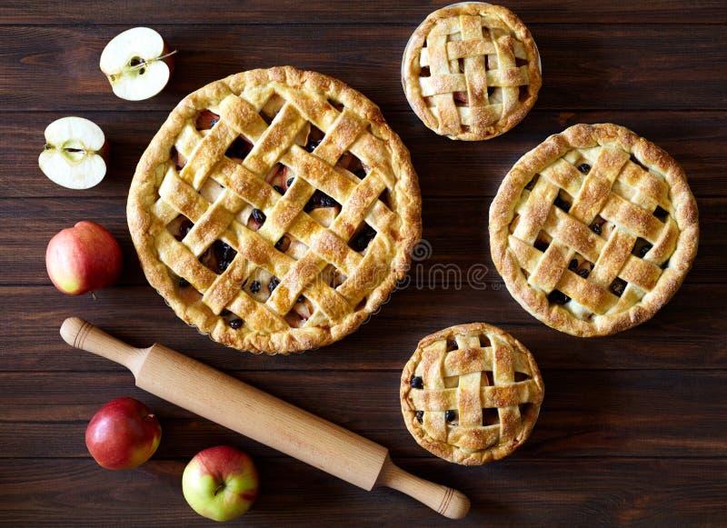Hemlagad äppelpajbakelse med russin och kanelbruna bageriprodukter på träbakgrundstextur Top beskådar traditionellt arkivbild