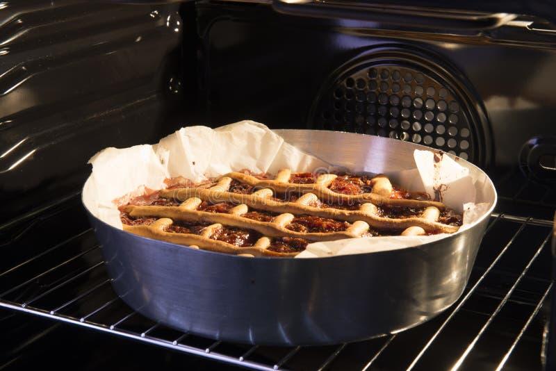 Hemlagad äpplekaka i pannan i ugnen italienska matlagningmatingredienser arkivbild