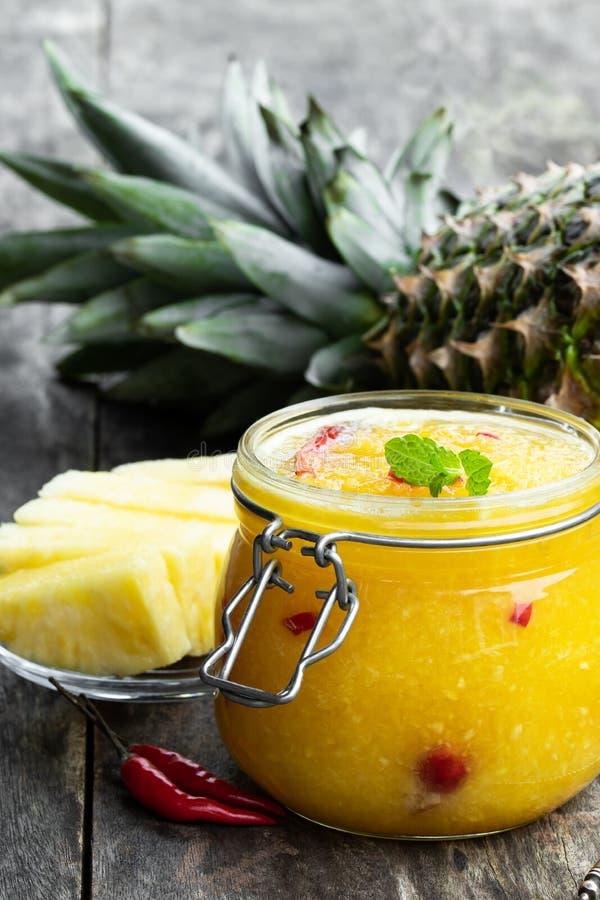 Hemlagad ananas- och f?r chilipeppar chutney i exponeringsglaskrus p? den gr?a tabellen royaltyfri fotografi