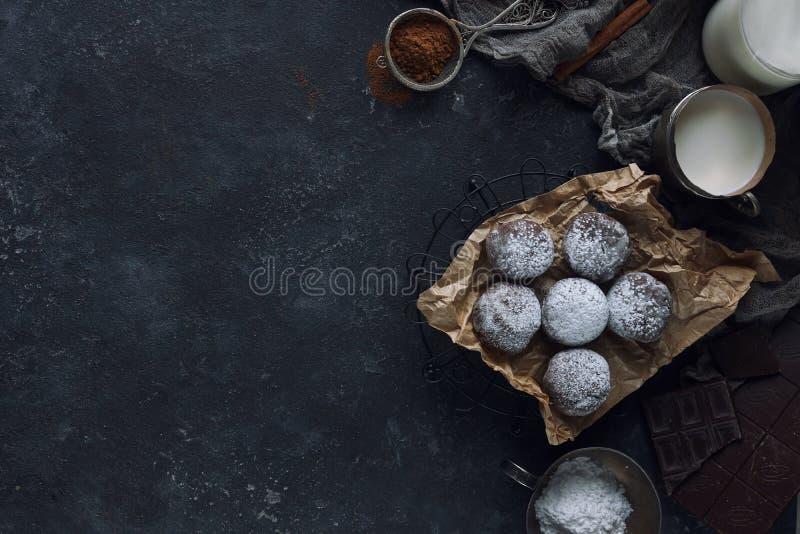 Hemlagad choklad rynkar i pudrat socker, chokladkakor med sprickor, och ett exponeringsglas av mjölkar royaltyfria bilder