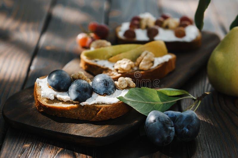 Hemlagad crostini med frukter, valnötter och ricotta royaltyfria bilder