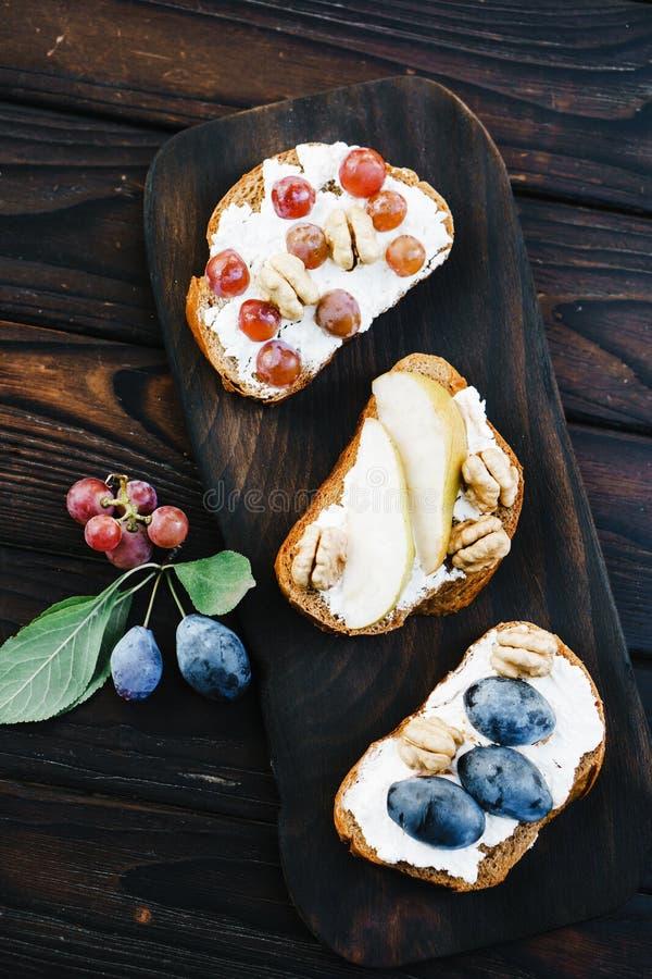 Hemlagad crostini med frukter, valnötter och ricotta arkivbild