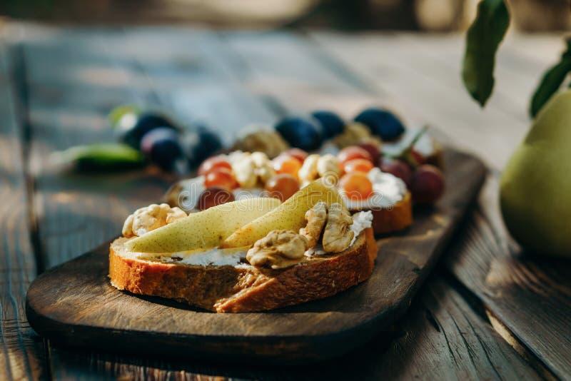 Hemlagad crostini med frukter, valnötter och ricotta arkivbilder