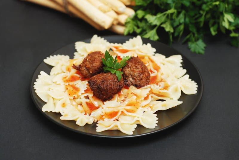 Hemlagad Farfalle pasta med köttbullar och sås på den svarta plattan sund mat arkivfoton