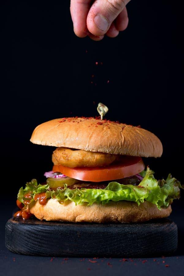 Hemlagad feg hamburgare på det mörk träbrädet och man& x27 för portion; s fingrar strila röd peppar arkivfoton