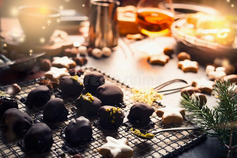 Hemlagad festlig konfekt, brända mandlar och tryfflar på mörk lantlig bakgrund med ingredienser Julsötsakbakelser royaltyfria foton