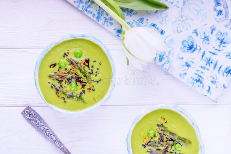 Hemlagad grön kräm- soppa med sparris, gröna ärtor, svart sesamfrö och pumpaolja på en vit bakgrund royaltyfria foton