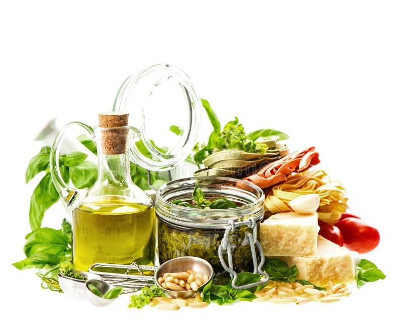 Hemlagad grön pestosås och ingredienser på vit royaltyfria foton