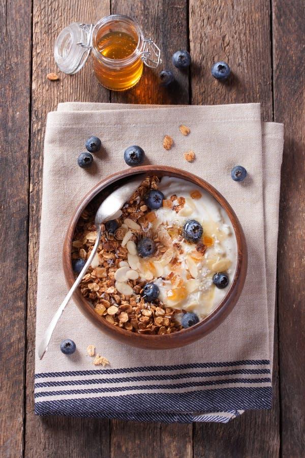 Hemlagad granola med muttrar, kanderade apelsiner, nya blåbär, yoghurt och honung royaltyfria bilder