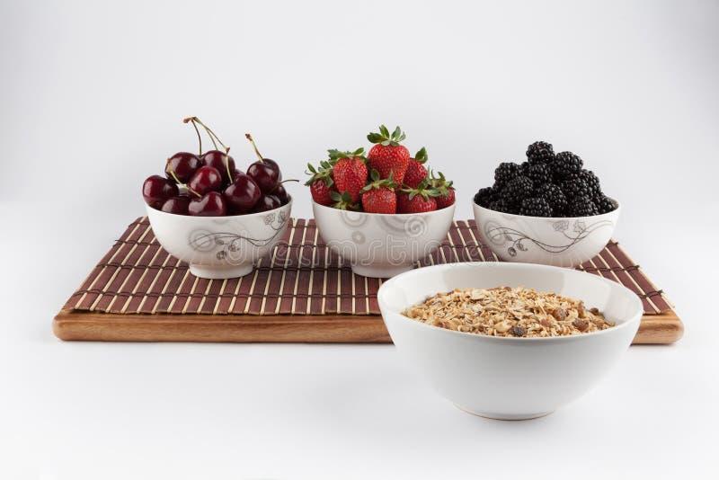 Hemlagad Granola och körsbär, jordgubbar och björnbär in arkivbild