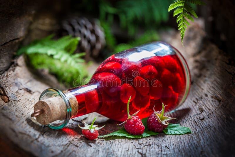 Hemlagad hallonlikör som göras av frukter och alkohol royaltyfri bild