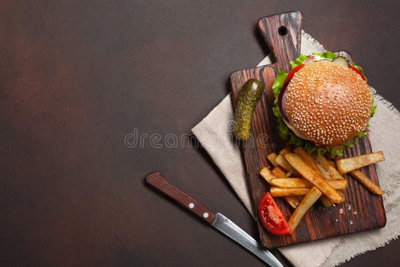 Hemlagad hamburgare med ingredienser n?tk?tt, tomater, gr?nsallat, ost, l?k, gurkor och franska sm?fiskar p? sk?rbr?da och rostig royaltyfria foton