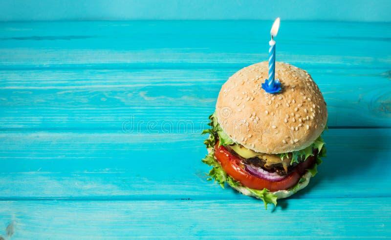 Hemlagad hamburgaregrillfestsmörgås med nötkött och den tända stearinljuset för födelsedagparti på blå bakgrund Begreppsferie arkivbilder