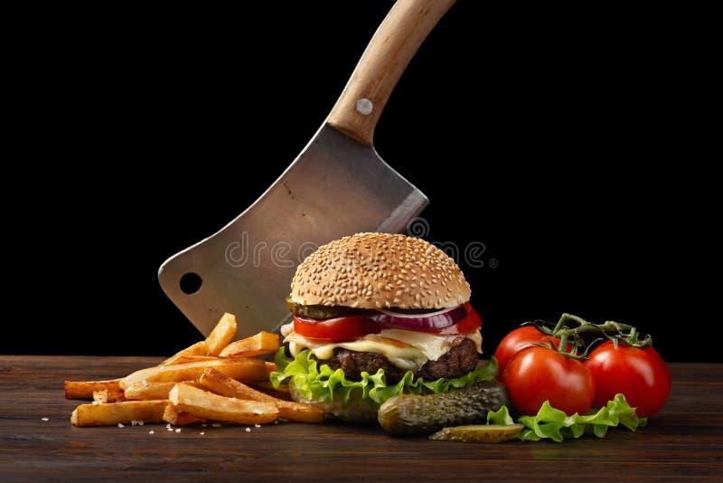 Hemlagad hamburgarenärbild med nötkött, tomaten, grönsallat, ost, löken och franska småfiskar på trätabellen I hamburgaren klibba royaltyfri foto