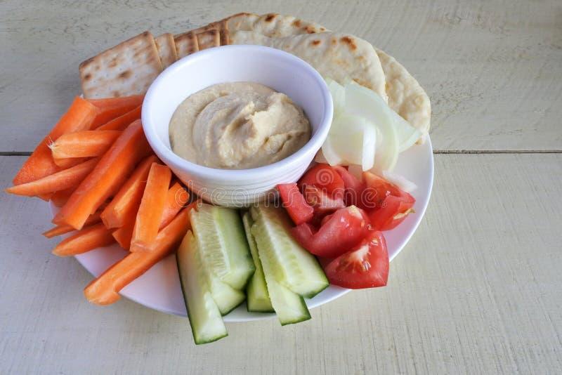 Hemlagad hummus med blandade nya grönsaker royaltyfri bild