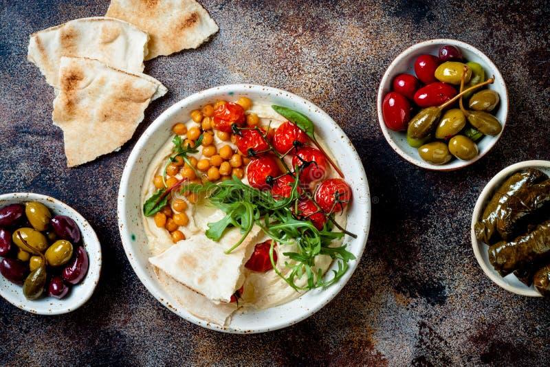 Hemlagad hummus med grillad k?rsb?rsr?da tomater, oliv, dolma och pitabr?d royaltyfri foto