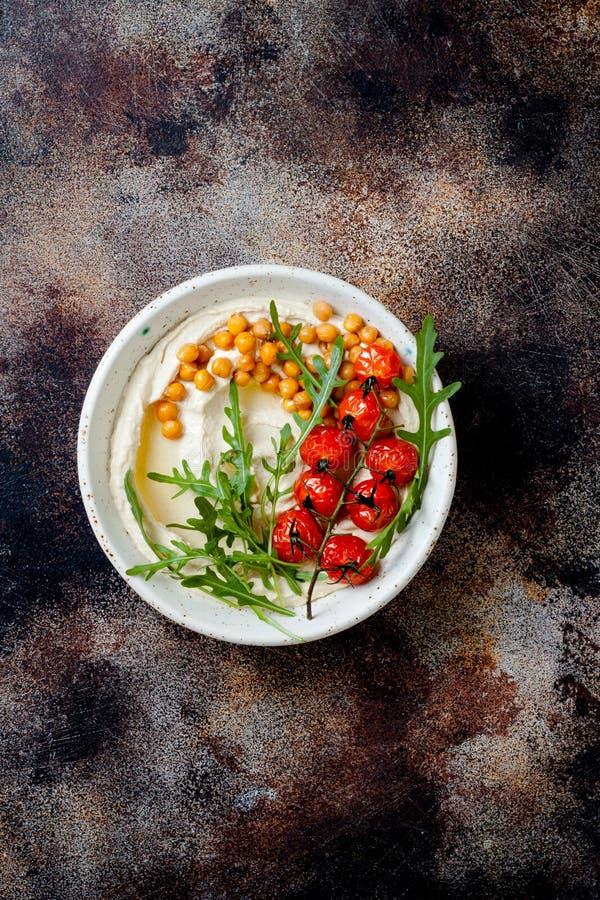 Hemlagad hummus med grillade k?rsb?rsr?da tomater Mitt - ?stlig traditionell och autentisk arabisk kokkonst arkivbilder