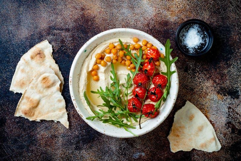 Hemlagad hummus med grillade k?rsb?rsr?da tomater Mitt - ?stlig traditionell och autentisk arabisk kokkonst royaltyfri foto