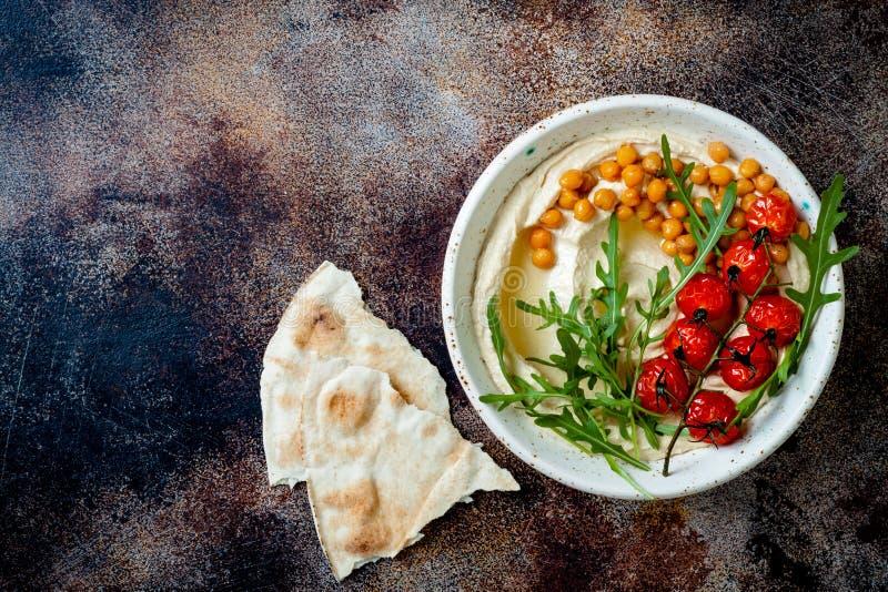 Hemlagad hummus med grillade k?rsb?rsr?da tomater och oliv Mitt - ?stlig traditionell och autentisk arabisk kokkonst fotografering för bildbyråer