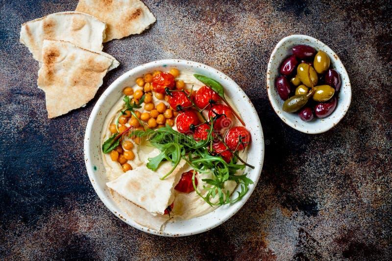 Hemlagad hummus med grillade k?rsb?rsr?da tomater och oliv Mitt - ?stlig traditionell och autentisk arabisk kokkonst arkivbild