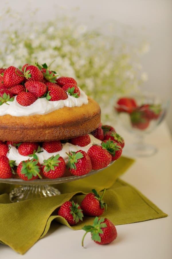 Hemlagad jordgubbekaka med kräm på en glass ställning royaltyfri foto