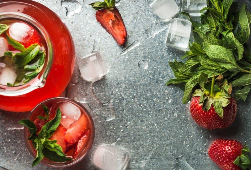 Hemlagad jordgubbelemonad med mintkaramellen, is och nya bär över metallmagasinbakgrund, bästa sikt, kopieringsutrymme arkivfoto
