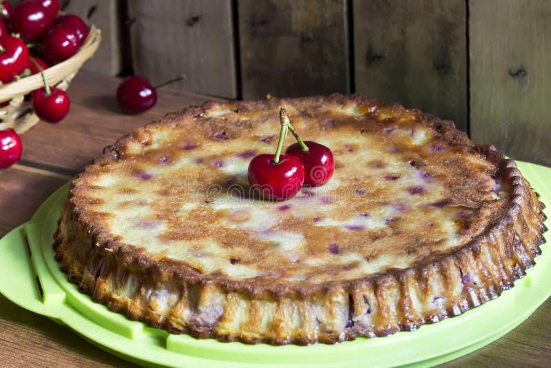 Hemlagad körsbärsröd fransk kaka med vanilj och svarta körsbär på trätabellen fotografering för bildbyråer