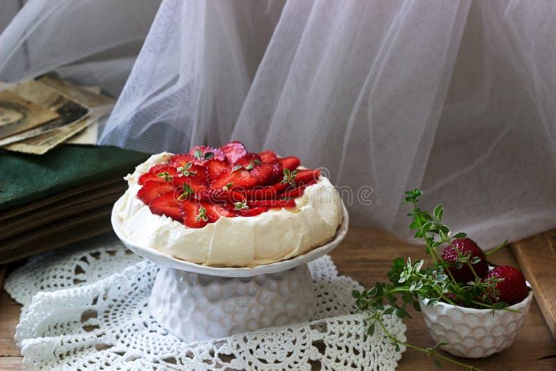 Hemlagad kaka f?r Pavlova mar?ng med jordgubbar och kr?m p? bakgrunden av ett gammalt fotoalbum Lantlig stil fotografering för bildbyråer