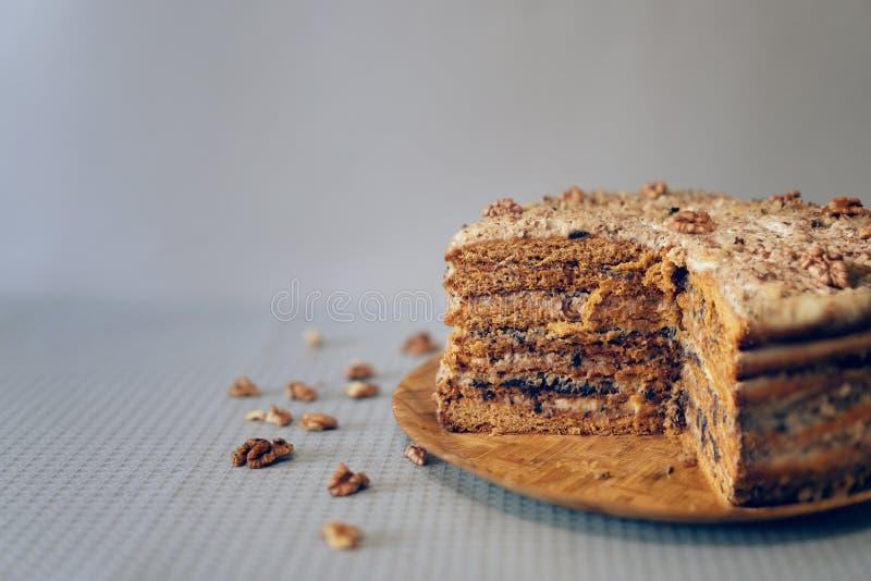 Hemlagad kaka som göras med kräm, muttrar och katrinplommonet på trämagasinet royaltyfri fotografi
