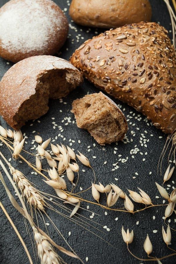 Hemlagad kavring som strilas med mjöl och olika korn, och frö på en svart bakgrund med spikelets av vete eller råg och royaltyfria foton