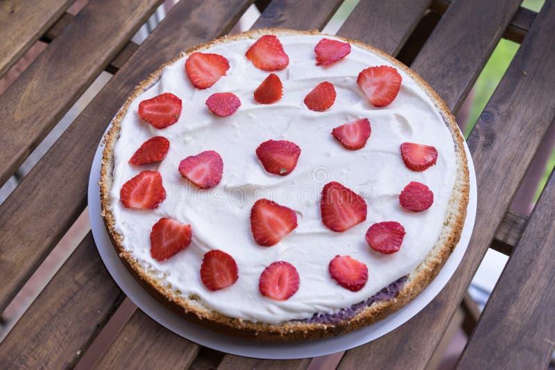 Hemlagad kräm- efterrätt för kaka för lager ny, färgrik och läcker, med saftiga jordgubbar, sötsak piskad kräm och kräm royaltyfri foto