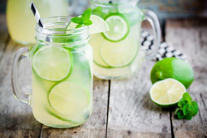 Hemlagad lemonad med limefrukt, mintkaramell i en murarekrus på en trätabell royaltyfri foto