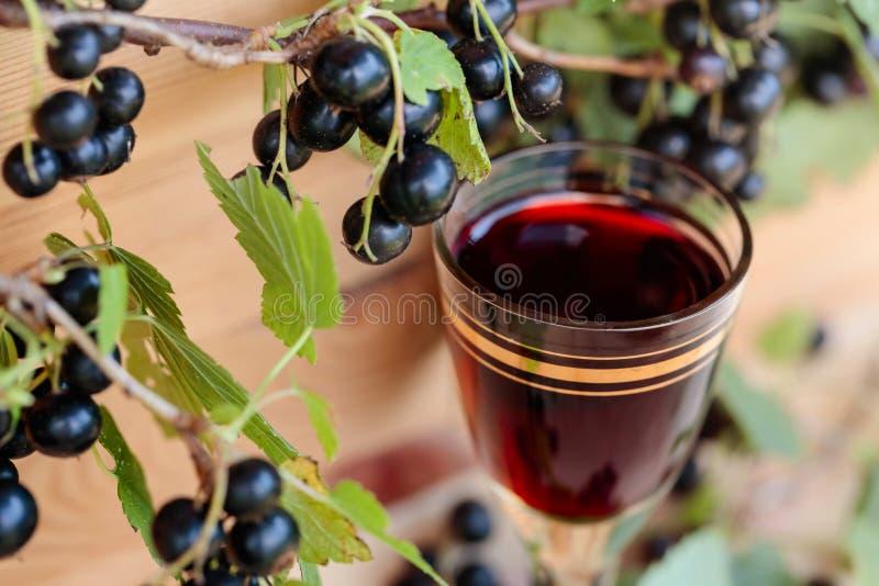 Hemlagad likör som göras från svarta vinbär och nya bär arkivbild