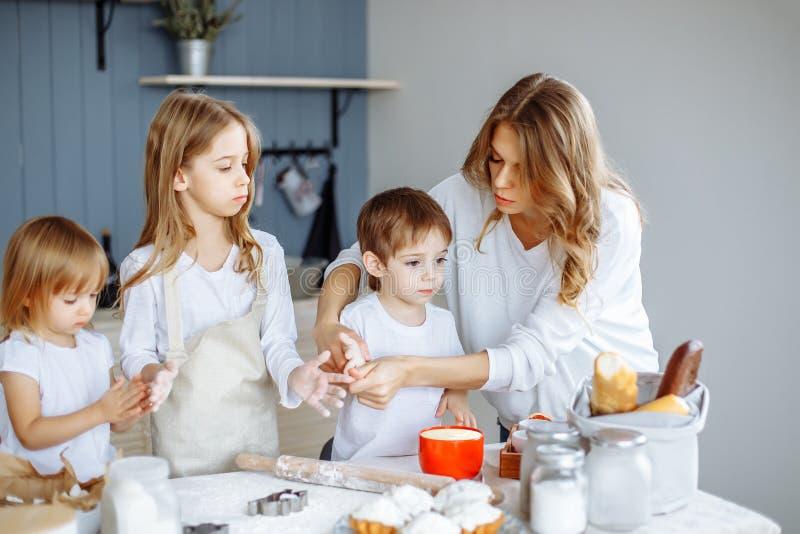 Hemlagad matlagning Den lyckliga familjen gör kakor tillsammans i köket royaltyfria foton