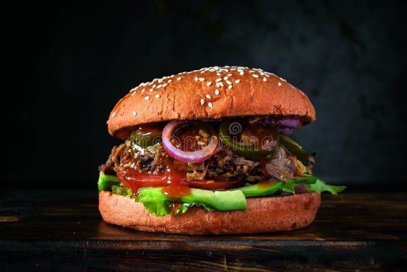 Hemlagad medelhavs- hamburgare med nötköttbringan, oliv, löken, avokadot och tabasco fotografering för bildbyråer