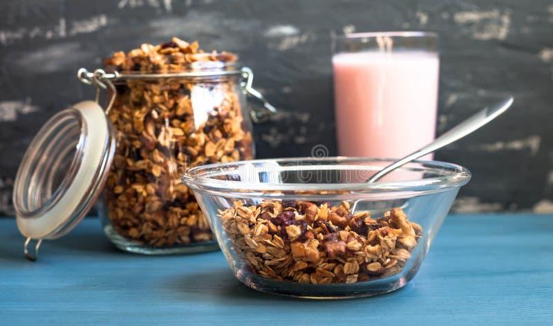 Hemlagad mysli med yoghurt i en platta på en blå bakgrund, sund frukost av havremjölmysli, muttrar, frö och torkat arkivbild
