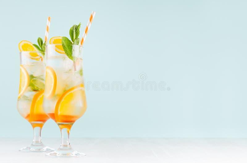 Hemlagad orange fruktsaft med den gr?na mintkaramellen, iskuber, sugr?r i misted genomskinligt exponeringsglas p? mjuk ljus paste royaltyfria bilder