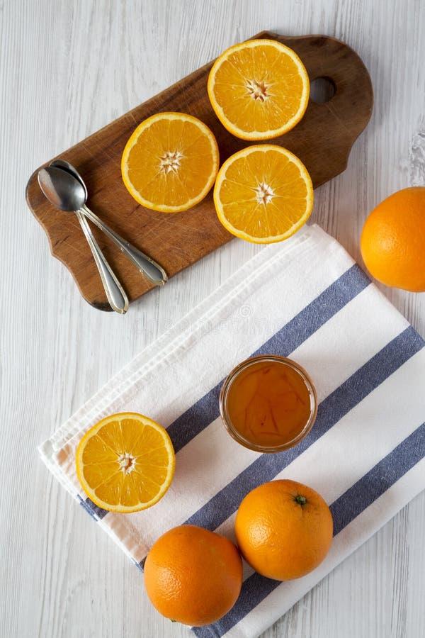 Hemlagad orange marmelade över vit träbakgrund, bästa sikt Lekmanna- lägenhet, över huvudet, från över royaltyfria foton