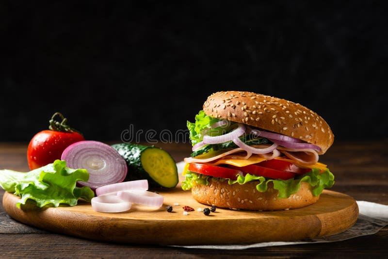 Hemlagad osthamburgare eller hamburgare med skinka, tomater, ost och gr?nsallat p? tr?br?de kopiera avst?nd Snabbmat f?r frukost  arkivbilder