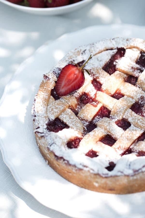 Hemlagad paj med jordgubbar på tabellen i trädgården Bakad söt bakelse för jordgubbepajkaka arkivbilder