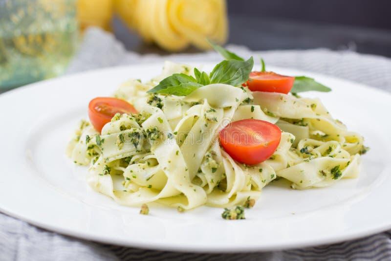 Hemlagad pasta från basilika och arugula med grön pesto i en vit platta på en mörk bakgrund lyx för livsstil för utmärkt mat för  royaltyfri foto