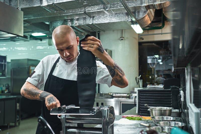 Hemlagad pasta Stående av den koncentrerade unga kocken som rullar en svart deg till och med pastamaskinen i restaurangen royaltyfri fotografi