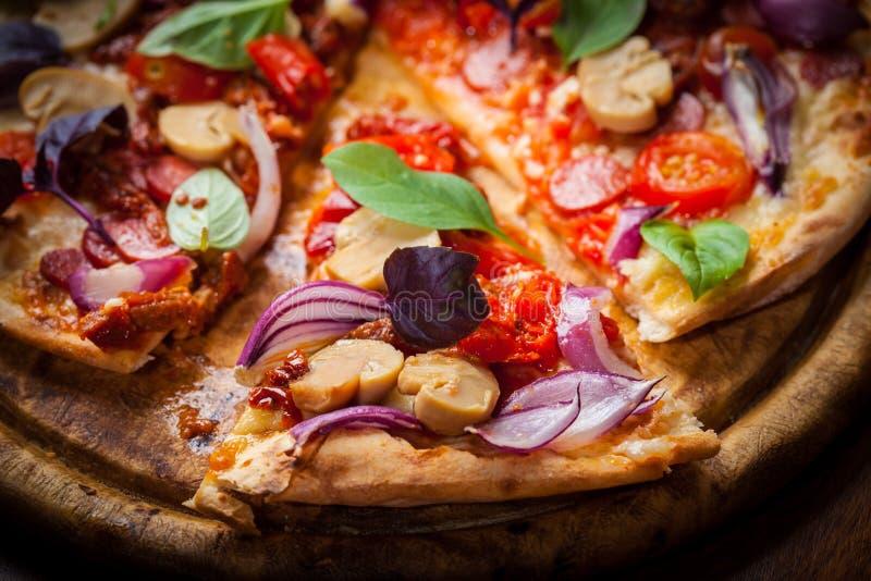 Hemlagad pizza med torkad tomater och salami royaltyfri foto
